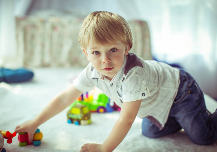 little cute boy in white shirt sits on floor and playing with to